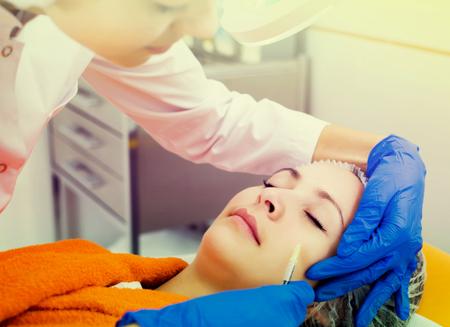 Doctora adulta utilizando inyección en procedimientos de belleza a cliente joven