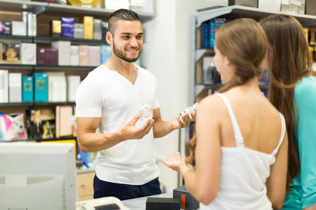 Smiling male store clerk serving purchaser at cash desk