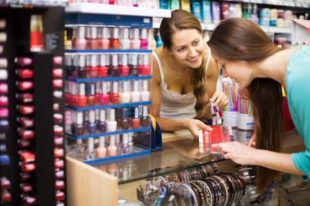 Smiling store clerk serving purchaser with nail polish at cash desk Stock Photo