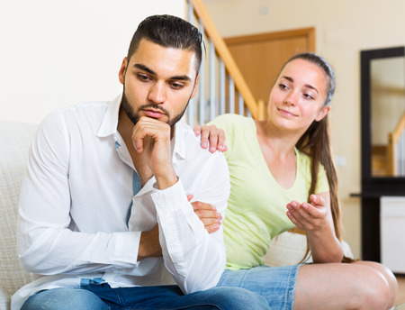 Unhappy american wife listening smiling husband