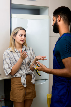 serviceman: Young housewife and black serviceman standing near fridge indoors