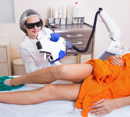 Diligent friendly  female client doing laser hair removal from legs