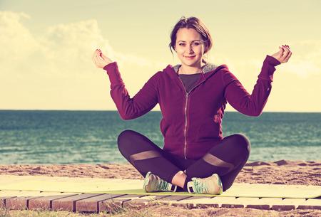 Portrait of happy young woman doing yoga asanas and pranayama at beach