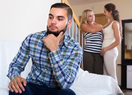 misunderstanding: Three displeased young friends having misunderstanding at home Stock Photo
