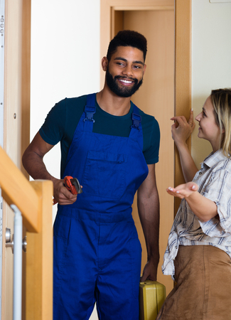 blue overall: White girl meeting African handyman in blue overall at the doorway