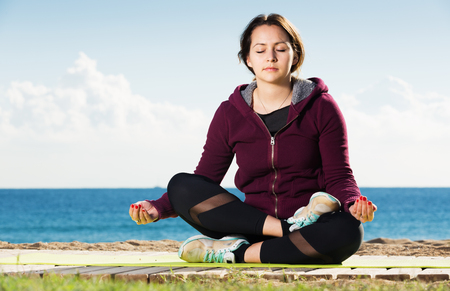 Cheerful young woman doing yoga asanas and pranayama at seaside Stock Photo
