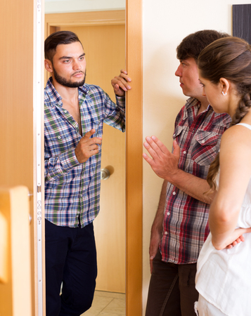 neighbor: Unhappy male neighbor standing at entrance and complaining about noise. Focus on the man
