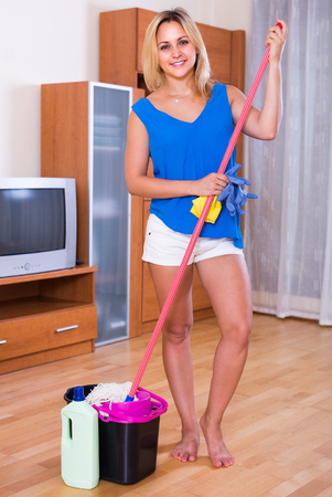 Cheerful smiling adult blonde girl washing floors at home using liquid detergent