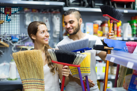 householder: Happy smiling young couple wants to buy broom at the household store. Selective focus