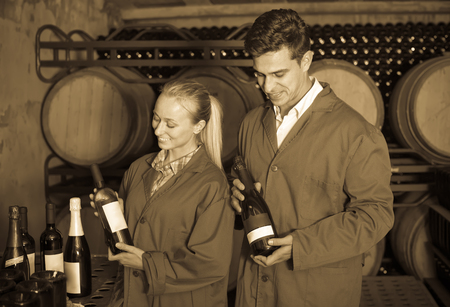 aging american: Two friendly winery employees in uniform holding bottles of wine in aging section in cellar Stock Photo