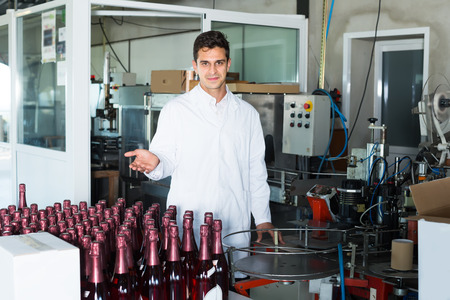 friendly man employee in uniform standing in final section of wine production on factory Stock Photo