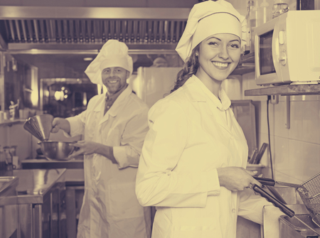 shef: Portrait of smiling chef and his young beautiful female helper at bistro kitchen Stock Photo