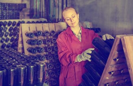 big cork: Portrait of smiling female wine maker wearing coat taking care of seasoning bottles in winery cellar Stock Photo