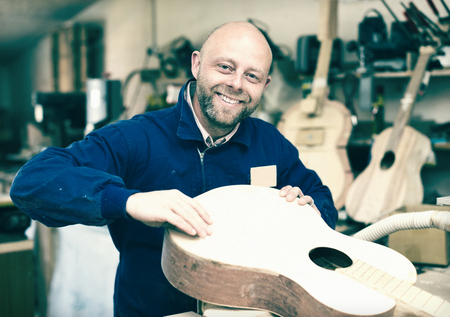 toolroom: Male craftsman working with unfinished guitar indoors Stock Photo