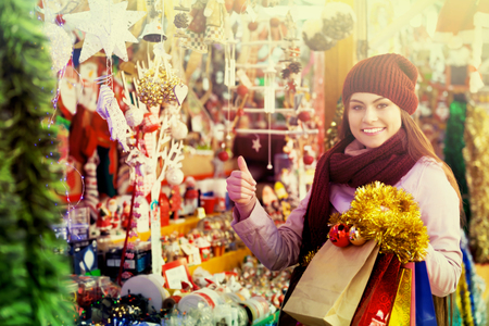 overspending: Portrait of young happy woman shopping at festive fair before Christmas Stock Photo