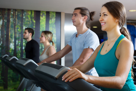 Group of adults people training on treadmills in gym