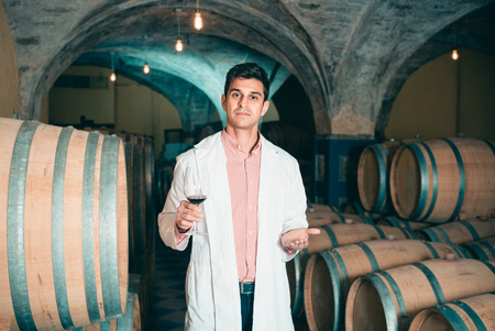 Professional taster of winery posing with  laboratorian wine in cellar