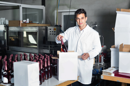 diligente: Glad positive diligent man in coat standing in packing section on winemaking factory