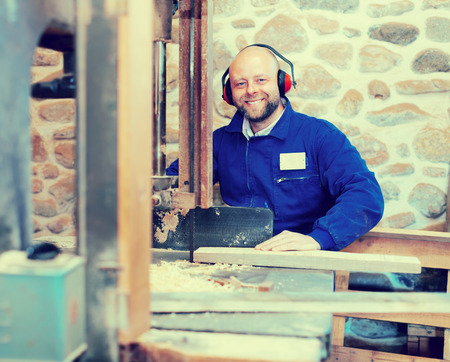 toolroom: Portrait of professional carpenter in a blue uniform wearing hearing protection working on a power-saw bench