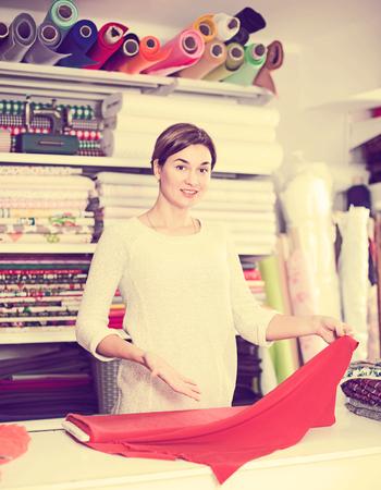 shop assistant: Female shop assistant measuring piece of cloth at drapery shop