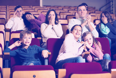 adrenaline rush: Scared of people and children enjoying scary film in in cinema house Stock Photo