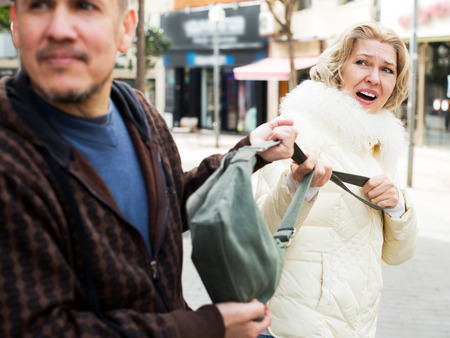 accosting: Elderly man pulling female bag, outdoors robbery at day time Stock Photo