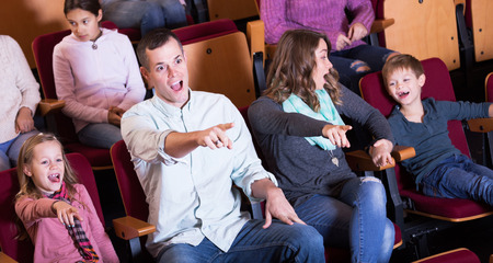 exciting: Group of young people watching exciting movie in cinema house Stock Photo