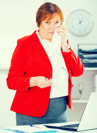 Senior female worker having problem in project in office Stock Photo
