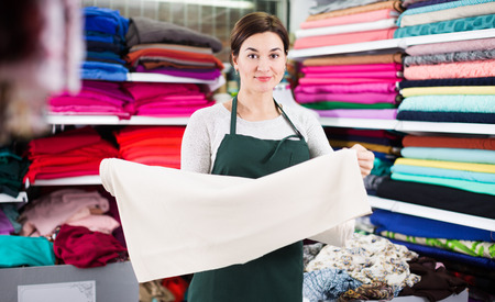 Smiling girl seller showing white fabric at drapery shop Stock Photo
