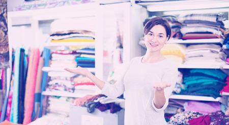 displaying: Young woman seller displaying various fabrics at drapery shop