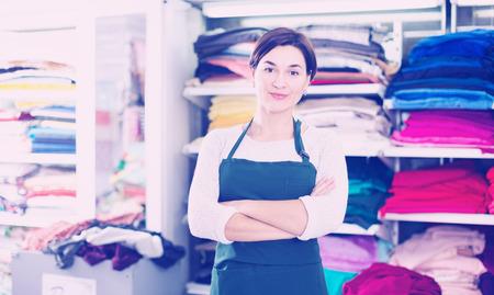 shop assistant: Female shop assistant demonstrating assortment at drapery shop Stock Photo