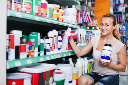 Glad woman customer looking for paint solvent in bottle in household store