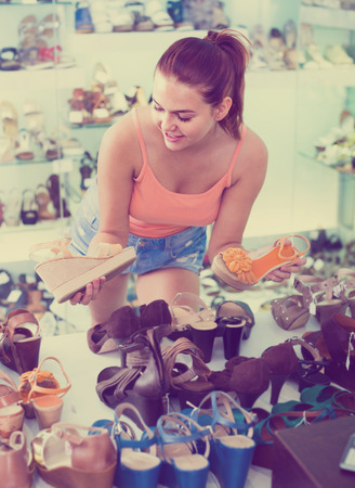 ?portrait of happy teenage girl looking after pair of shoes in fashion store Stock Photo