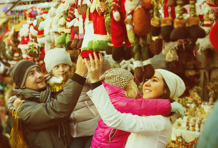 5s: Happy young parents with kids choosing X-mas decorations in market. Focus on woman Stock Photo