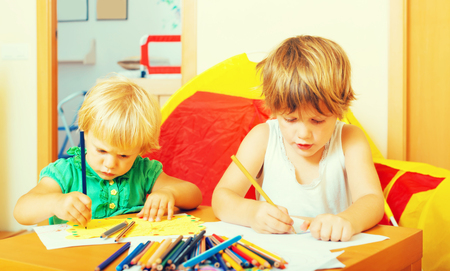 Siblings playing with pencils in home interior
