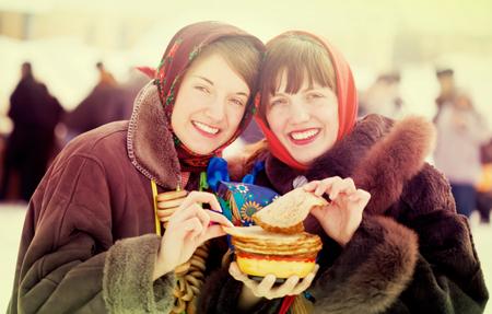 Young women eating pancake during  Pancake Week outdoor
