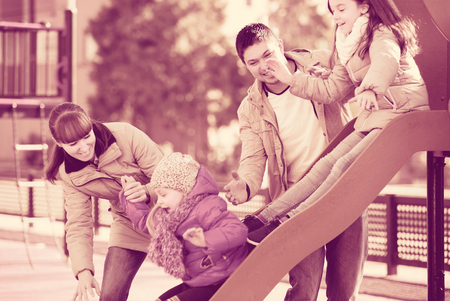 Smiling adult parents playing with little daughters at slide of playground. Focus on man Stock Photo