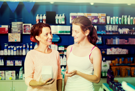 buying questions: Glad mother with teenager daughter choosing healthcare products in drug store
