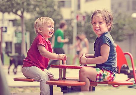 5s: Two happy little  american sisters on teetering board outdoor