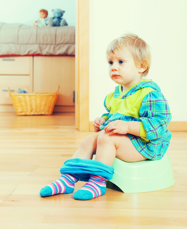 Toddler sitting on green potty in home