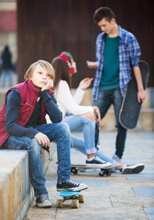 unfaithfulness: Envy male teen sitting aside of girlfriend talking with boy Stock Photo