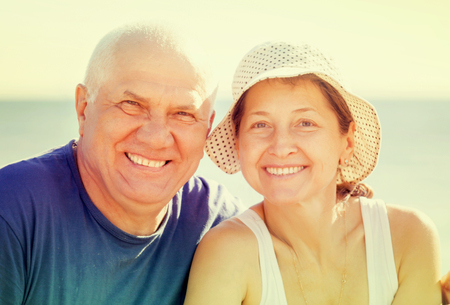 the sixties: mature couple together at sea beach