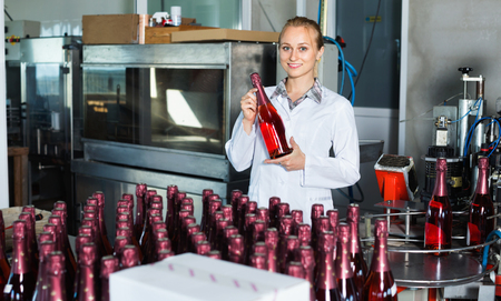 Young woman employee in coat working on final section of wine production on factory Stock Photo