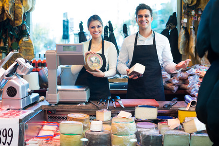 Two  happy workers selling cheese in delicatessen store and smiling