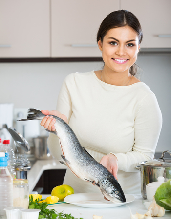 domestic kitchen: happy spanish girl holding rainbow trout in domestic kitchen