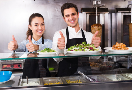 restaurant staff: Smiling young restaurant staff posing at kebab counter and smiling Stock Photo