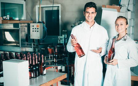Two colleagues holding newly produced bottles of wine on winery manufactory Stock Photo