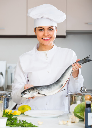 jorobado: Happy smiling female cook in white uniform preparing big fish in restaurant Foto de archivo