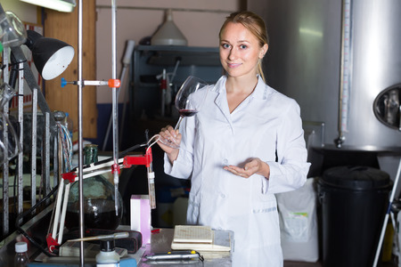 cheerful female specialist checking wine fermentation in winery laboratory Stock Photo
