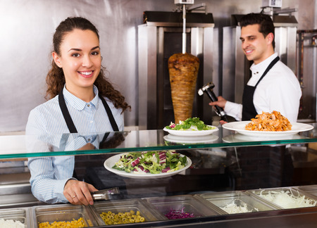 restaurant staff: Smiling restaurant staff posing at kebab counter and smiling Stock Photo